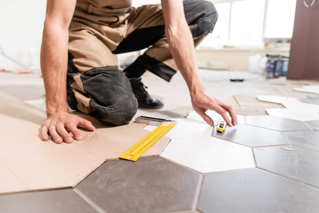 Male worker makes measurements and installing new wooden laminate flooring. The combination of wood panels of laminate and ceramic tiles in the form of honeycomb. Kitchen renovation.
